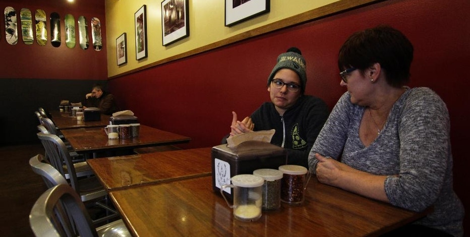 In this Jan. 9, 2017, photo, Andrea Ledesma, second from right, talks with her mother, Cheryl Romanowski, at Classic Slice pizza restaurant, where Ledesma works, in Milwaukee. Ledesma, 28, says her parents owned a house and were raising kids by her age. Not so for her, even though she has a college degree. With a median household income of $40,581, millennials earn 20 percent less than boomers did at the same stage of life, despite being better educated, according to a new analysis of Federal Reserve data by the advocacy group Young Invincibles. (AP Photo/Carrie Antlfinger)
