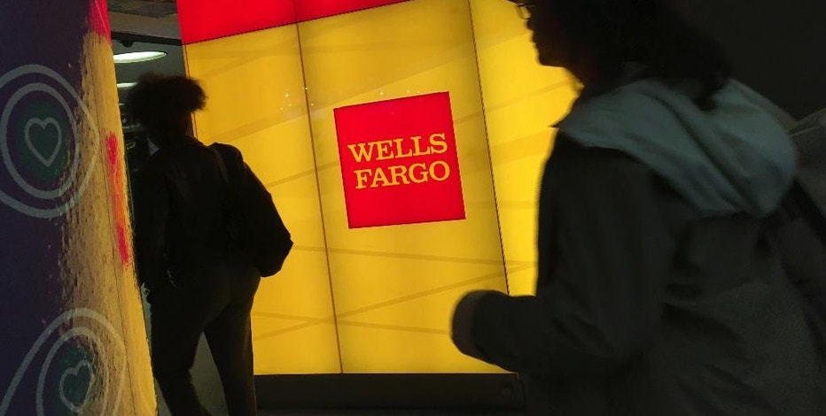 In this Thursday, Oct. 13, 2016, photo, commuters walk by a Wells Fargo ATM location at New York's Penn Station. On Friday, Jan. 13, 2017, Wells Fargo reports financial results. (AP Photo/Swayne B. Hall)