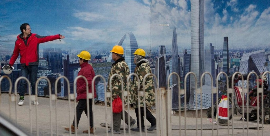 A construction worker directs others as they walk past an artist's impression of the Central Business District under construction in Beijing, China, Monday, Jan. 16, 2017. The International Monetary Fund on Monday raised its growth forecast for China but warned rising debt that has prompted concern about the country's finances increase the risk of a sharper slowdown. (AP Photo/Ng Han Guan)