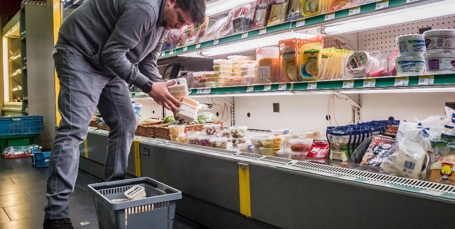 "A worker removes expired food in a local supermarket in Brussels on Monday, Jan. 16, 2017.  The European Court of Auditors has chided the European Union's executive branch in a report, ""Combating Food Waste,"" that decries the bloc's lack of effort in reducing the food waste, estimating the EU wastes 88 million tons of food per year.  (AP Photo/Geert Vanden Wijngaert)"