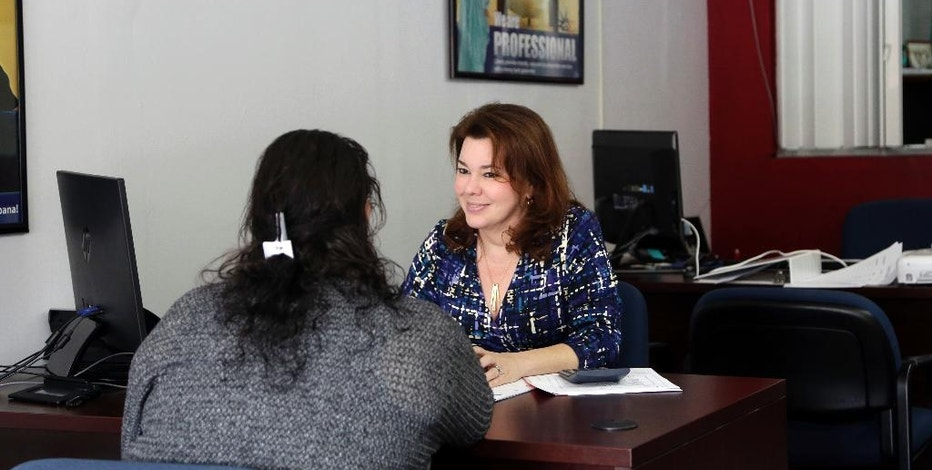 In this Wednesday, Jan. 11, 2017, photo, Maritza Montejo, right, works with a client at Liberty Tax Service in Miami. Tax preparers do a big chunk of America's tax returns, more than 80 million a year, according to the IRS. (AP Photo/Lynne Sladky)