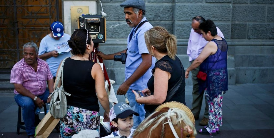 In this Dec. 1, 2016 photo, photographer Luis Maldonado talks to a client next to his old wooden box camera in Plaza de Armas of Santiago, Chile. Because most people are unwilling to pay more for a box camera photograph, Maldonado ultimately had to buy a digital camera and a small printer to make cheaper photographs. (AP Photo/Esteban Felix)