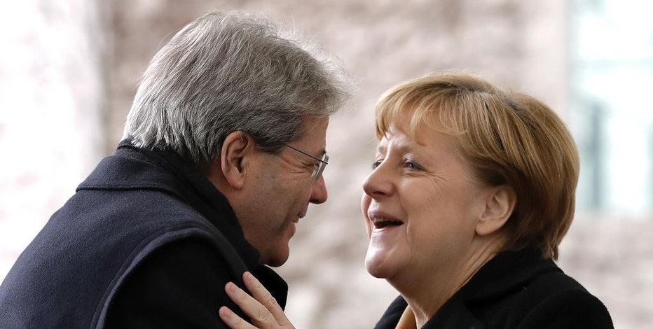 German Chancellor Angela Merkel, right, welcomes the Prime Minister of Italy Paolo Gentiloni, left, for a meeting at the chancellery in Berlin, Germany, Wednesday, Jan. 18, 2017. (AP Photo/Michael Sohn)