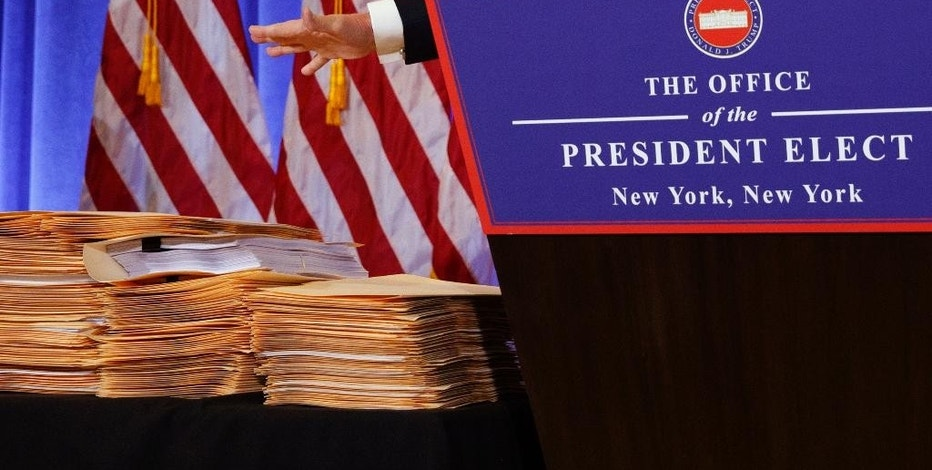 "FILE - In this Wednesday, Jan. 11, 2017, file photo, President-elect Donald Trump gestures next to stacks of manila envelopes he says contain documents formalizing new business arrangements, while speaking during a news conference in the lobby of Trump Tower in New York. Trump has vowed his company will do ""no new foreign deals"" while he is president, but he left vague just how to define ""new"" and ""deals."" (AP Photo/Evan Vucci, File)"