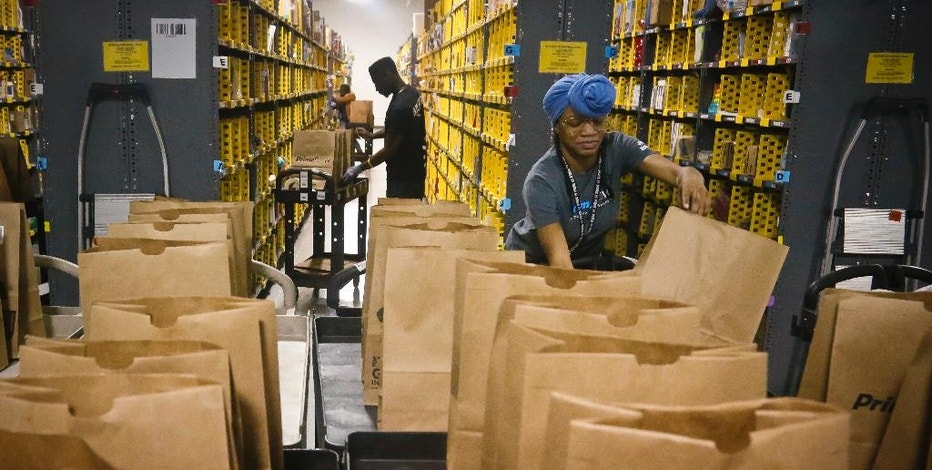 FILE - In this Wednesday, Dec. 21, 2016, file photo, Miracle Stewart, right, an employee of Amazon PrimeNow, prepares bags to fill with orders from customers making purchases, at a distribution hub in New York. From Wal-Mart to General Motors to Amazon, a growing number of the world's largest companies appear to be trying to get in step with President-elect Donald Trump's demand that employers hire and keep jobs at home. (AP Photo/Bebeto Matthews, File)