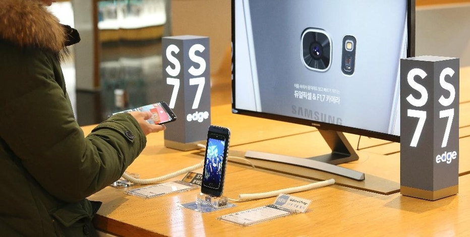 In this Monday, Jan. 23, 2017 photo, a visitor tries out a Samsung Electronics Galaxy S7 Edge smartphone at its shop in Seoul, South Korea. Samsung Electronics said on Tuesday, Jan. 24, its fourth quarter earnings more than doubled over a year earlier thanks to its brisk chip business. (AP Photo/Ahn Young-joon)