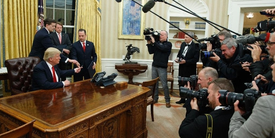 In this Jan. 20, 2017, photo, President Donald Trump hands over his pen after signing his first executive order in the Oval Office of the White House in Washington. It's the first full work week for the Trump administration, and the talk is all about emoluments, executive orders, a border tax, TPP and much more. (AP Photo/Evan Vucci)