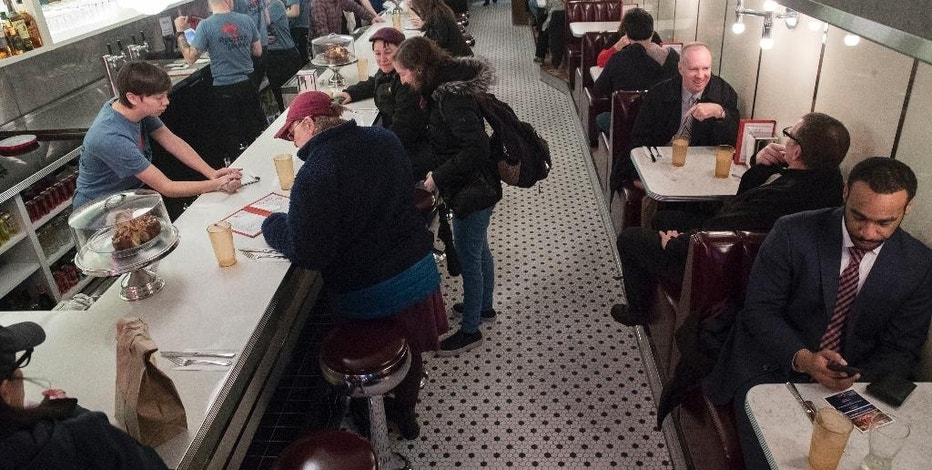 People gather for an afternoon meal at Rooster Soup Co. in Philadelphia, Monday, Jan. 23, 2017. The restaurateurs have found a valuable use for their discarded chicken backs: making soup for charity. All proceeds after expenses will benefit Broad Street Ministry, a local nonprofit serving the hungry and homeless. (AP Photo/Matt Rourke)