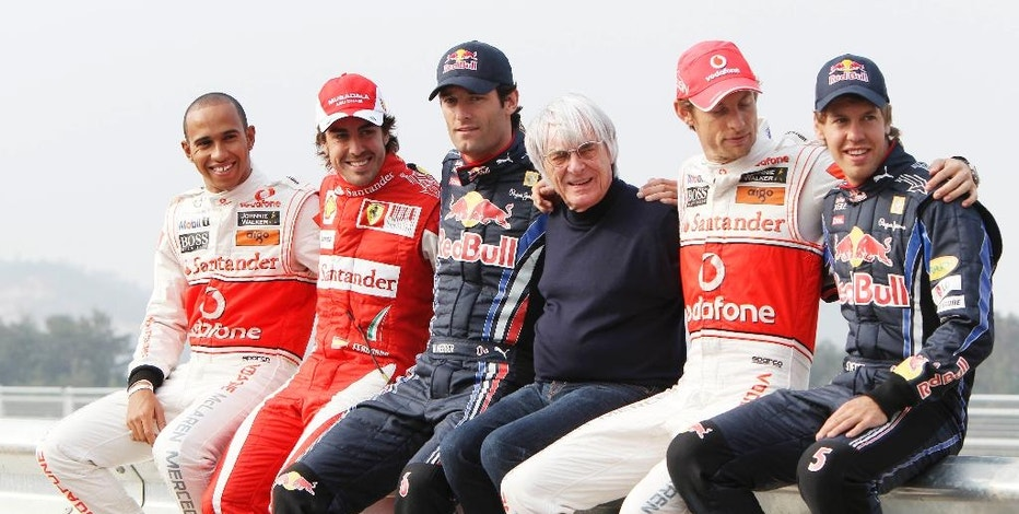 FILE - This is a Thursday, Oct. 21, 2010 file photo of Formula One boss Bernie Ecclestone, centre, poses for a photo with from left, McLaren  driver Lewis Hamilton,  Ferrari driver Fernando Alonso,  Red Bull driver Mark Webber, McLaren driver Jenson Button , 2nd right,  and Red Bull Sebastian Vettel at the Korean International Circuit venue for the Korean Grand Prix in Yeongam, South Korea, Bernie Ecclestone's reign of Formula One ended after Liberty Media officially completed its takeover of the series on Monday Jan 23, 2017. (AP Photo/Mark Baker, File)