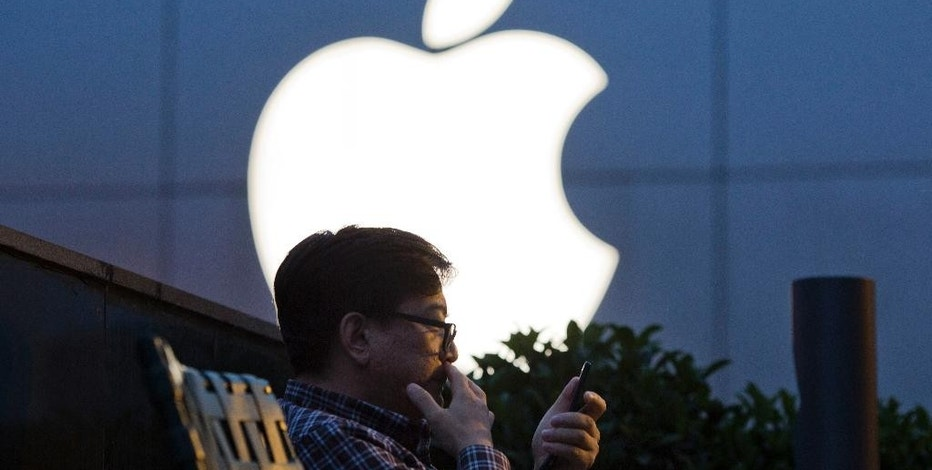 FILE - In this May 13, 2016 file photo, a man uses his mobile phone near an Apple store logo in Beijing, China. Apple Inc. has filed suit in China challenging Qualcomm Inc.'s fees for technology used in smartphones two years after Chinese regulators fined the chipmaker for its licensing practices. Two suits filed by the iPhone maker accuse Qualcomm of abusing its control over essential technology to charge excessive licensing fees, a Beijing court said on its microblog. (AP Photo/Ng Han Guan, File)