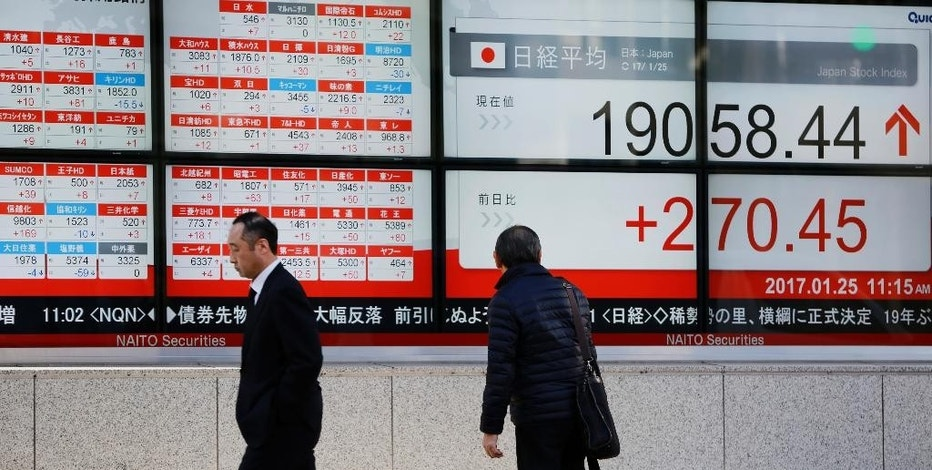 A man looks at an electronic stock board showing Japan's Nikkei 225 index at a securities firm in Tokyo, Wednesday, Jan. 25, 2017. Asian markets gained Wednesday, building on Wall Street's overnight rally. Shares in Japan rose on stronger-than-expected trade data and a weaker yen. (AP Photo/Eugene Hoshiko)