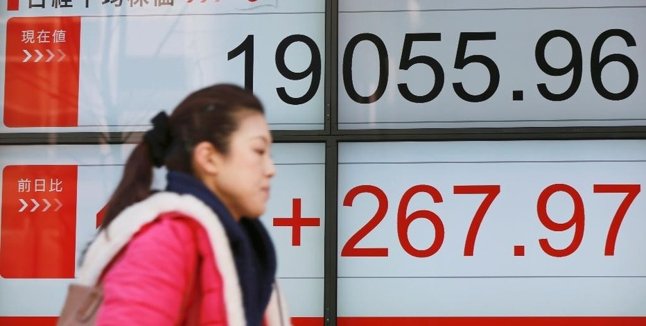A woman walks past an electronic stock board showing Japan's Nikkei 225 index at a securities firm in Tokyo, Wednesday, Jan. 25, 2017. Asian markets gained Wednesday, building on Wall Street's overnight rally. Shares in Japan rose on stronger-than-expected trade data and a weaker yen. (AP Photo/Eugene Hoshiko)