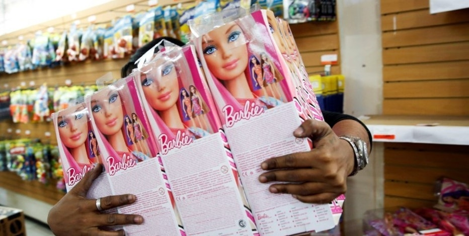 A worker carries Barbie dolls to put them on the shelves at a toy store in Caracas November 14, 2014. REUTERS/Carlos Garcia Rawlins/File Photo