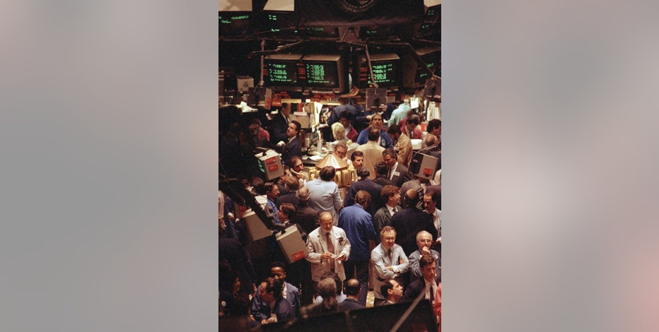 FILE - In this April 17, 1991, file photo, traders work on the floor of the New York Stock Exchange as trading pushed the Dow Jones industrial average over the 3,000-point mark. The Dow Jones industrial average closed above 20,000 points for the first time Wednesday, Jan. 25, 2017, two months after its first close above 19,000. (AP Photo/Bebeto Matthews, File)