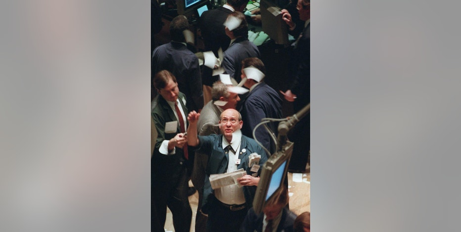 FILE - In this Nov. 21, 1995, file photo, a New York Stock Exchange trader throws tickets into the air on the floor of the exchange as it closes above the 5,000-point mark for the first time, in New York. The Dow Jones industrial average closed above 20,000 points for the first time Wednesday, Jan. 25, 2017, two months after its first close above 19,000. (AP Photo/Adam Nadel, File)