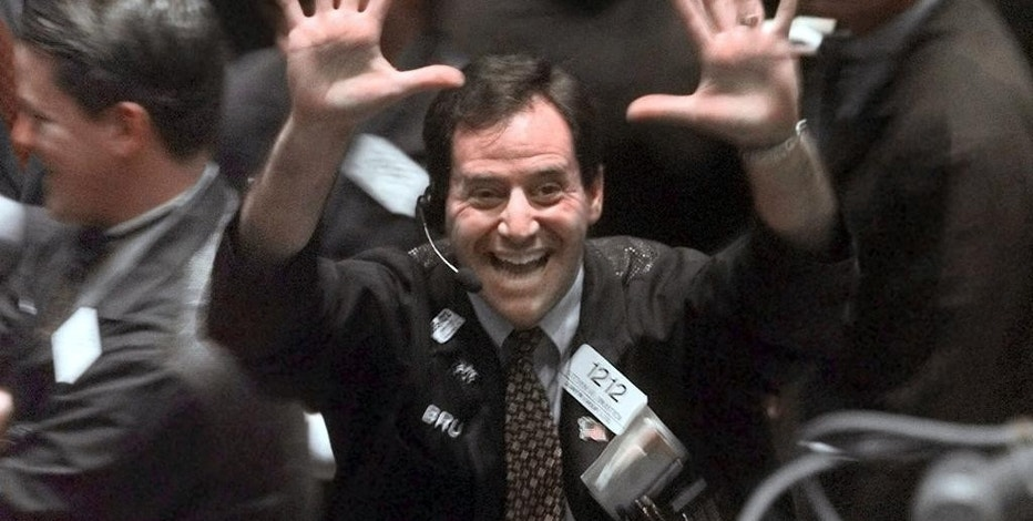 FILE - In this March 29, 1999, file photo, a trader smiles on the floor of the New York Stock Exchange while holding up 10 fingers after the Dow ended the day above 10,000 points for the first time. The Dow Jones industrial average closed above 20,000 points for the first time Wednesday, Jan. 25, 2017, two months after its first close above 19,000. (AP Photo/Adam Nadel, file)