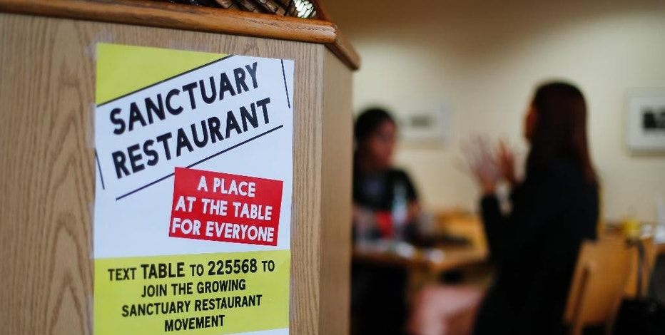 "In this Wednesday, Jan. 18, 2017 photo, a sanctuary restaurant sign is shown at Russell Street Deli in Detroit. Dozens of restaurants are seeking ""sanctuary"" status, a designation owners hope will help protect employees in an immigrant-heavy industry and tone down fiery rhetoric sparked by the presidential campaign. (AP Photo/Paul Sancya)"