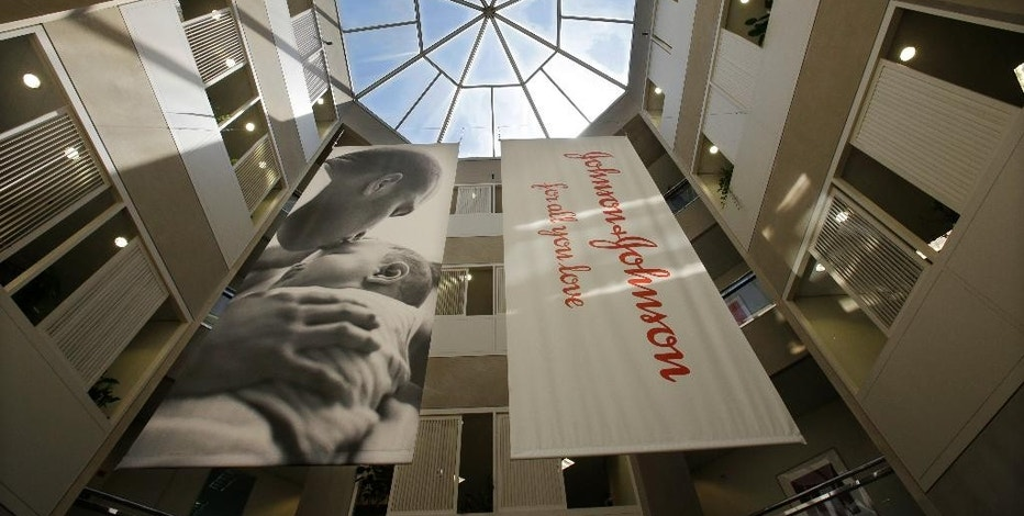FILE - In this July 30, 2013, file photo, large banners hang in an atrium at the headquarters of Johnson & Johnson in New Brunswick, N.J. In a deal announced Thursday, Jan. 26, 2017, Johnson & Johnson is buying Swiss pharmaceutical Actelion in a $30 billion deal that will boost its treatments for life-threatening high blood pressure conditions. (AP Photo/Mel Evans, File)