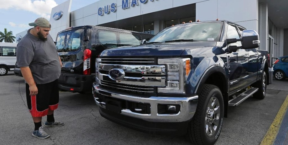 In this Tuesday, Jan. 17, 2017, photo, a potential customer looks at a 2017 Ford F-250 Lariat FX4 at a Ford dealership, in Hialeah, Fla. Ford Motor Company reports financial results Thursday, Jan. 26, 2017. (AP Photo/Alan Diaz)