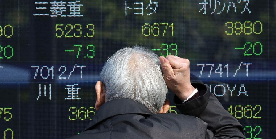 A man looks at an electronic stock board of a securities firm in Tokyo, Monday, Jan. 30, 2017. Shares fell in Japan and Australia on uncertainty over the potential impact of U.S. President Donald Trump's travel ban on seven Muslim-majority countries and other immigration actions. (AP Photo/Koji Sasahara)
