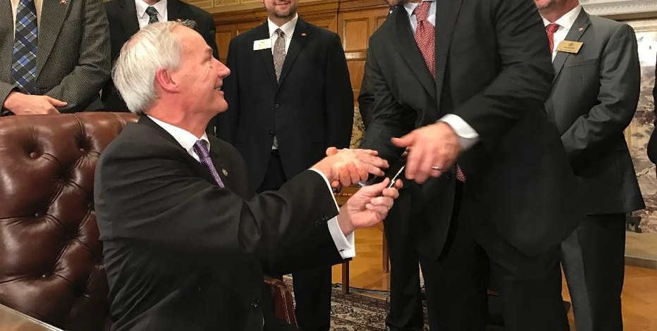 Arkansas Gov. Asa Hutchinson, left, shakes hands with Senate President Jonathan Dismang on Wednesday, Feb. 1, 2017, after signing legislation outlining a $50 million tax cut for thousands of low-income residents. A Senate panel endorsed a separate proposal aimed at forcing Amazon to collect state sales taxes, and lawmakers are eyeing the potential revenue from the move to help pay for future income tax cuts. (AP Photo by Andrew DeMillio)