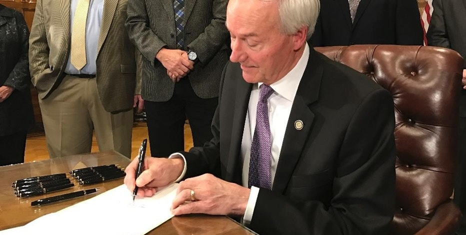 Arkansas Gov. Asa Hutchinson, signs into law legislation outlining a $50 million tax cut for thousands of low-income residents in Little Rock, Ark. A Senate panel endorsed a separate proposal aimed at forcing Amazon to collect state sales taxes, and lawmakers are eyeing the potential revenue from the move to help pay for future income tax cuts. (AP Photo by Andrew DeMillio)