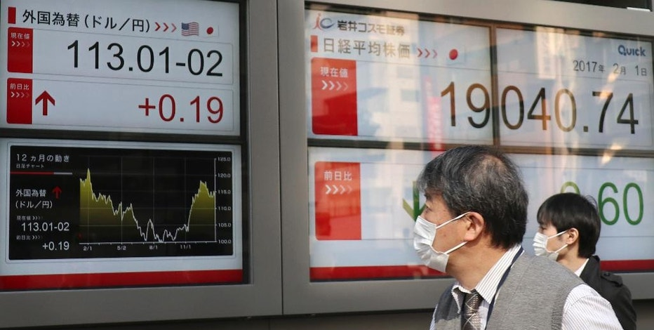 Men look at an electronic stock indicator of a securities firm showing the currency rate of the U.S. dollar that is traded at 113.01-02 yen in Tokyo, Wednesday, Feb. 1, 2017. Shares were mostly higher in Asia on Wednesday, lifted by upbeat manufacturing data from China and Japan. (AP Photo/Shizuo Kambayashi)