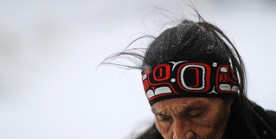 "FILE- Nov. 29, 2016, file photo, Grandma Redfeather of the Sioux Native American tribe walks in the snow to get water at the Oceti Sakowin camp where people have gathered to protest the Dakota Access oil pipeline in Cannon Ball, N.D. ""It's for my people to live and so that the next seven generations can live also,"" said Redfeather of why she came to the camp. ""I think about my grandchildren and what it will be like for them."" North Dakota Sen. John Hoeven said Tuesday, Jan. 31, 2017, that the Acting Secretary of the Army has directed the Army Corps of Engineers to proceed with an easement necessary to complete the Dakota Access pipeline. (AP Photo/David Goldman, File)"