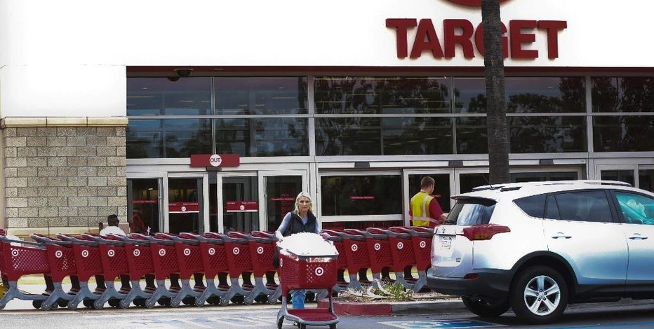 In this Thursday, May 26, 2016, photo, a woman pushes her shopping cart as an employee pulls a long line of carts outside a Target store  in Encinitas, Calif.  More than 100 retailers, including Wal-Mart and Target as well as key trade associations, are launching a new coalition aimed at fighting a Republican proposal on how imports get taxed, which they believe would harm their businesses. (AP Photo/Lenny Ignelzi)