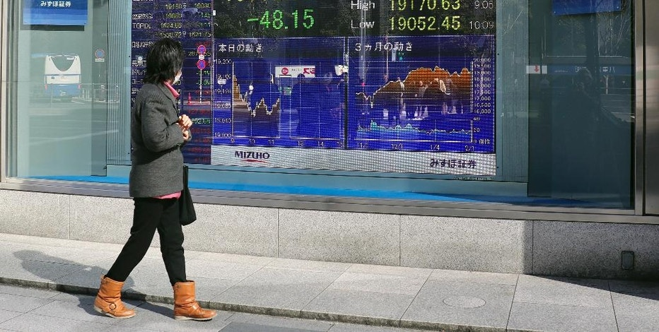 A woman looks at an electronic stock indicator of a securities firm in Tokyo, Thursday, Feb. 2, 2017. Asian markets wavered and the dollar lost some steam Thursday after the Fed kept its key lending rate on hold as expected at its latest policy meeting. (AP Photo/Shizuo Kambayashi)