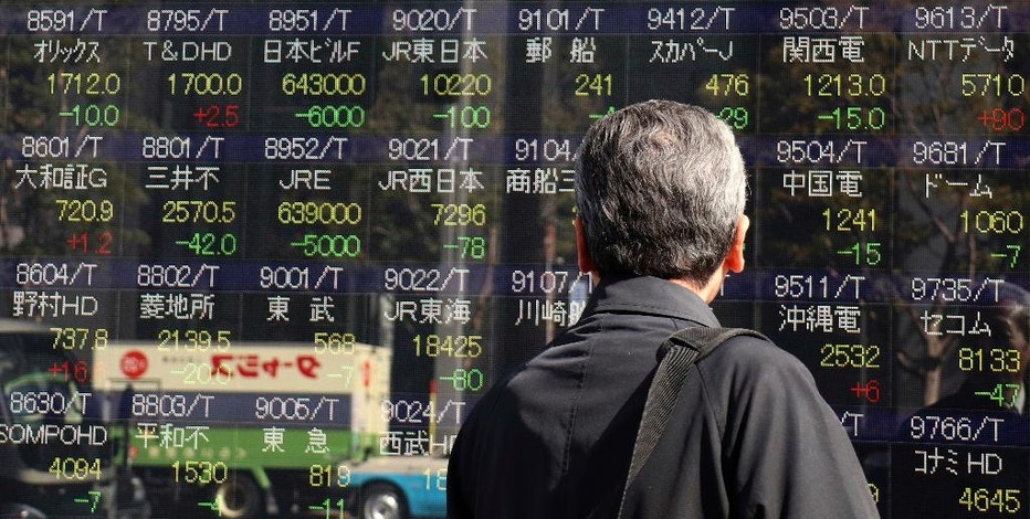 A man looks at an electronic stock indicator of a securities firm in Tokyo, Thursday, Feb. 2, 2017. Asian markets wavered and the dollar lost some steam Thursday after the Fed kept its key lending rate on hold as expected at its latest policy meeting. (AP Photo/Shizuo Kambayashi)