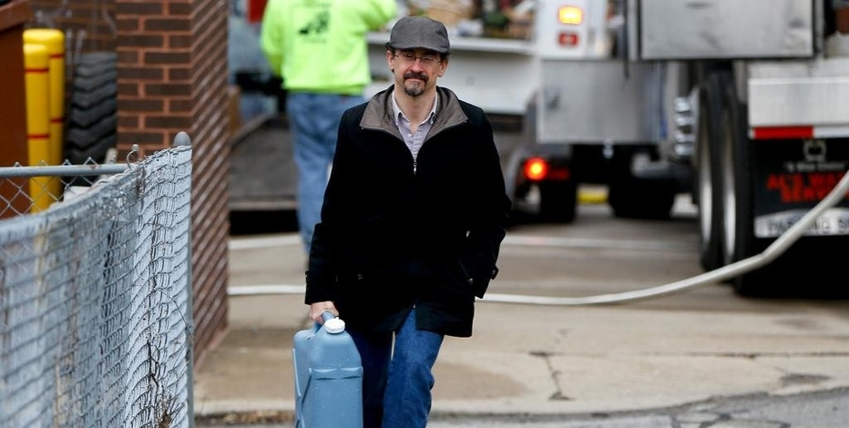 Tim Stuhldeher carries a container of water to his stepmother's house after filling it at a city fire station in the Lawrenceville section of Pittsburgh where the city made water available for the public on Wednesday, Feb. 1, 2017. The city set up over a dozen spots across town to distribute potable water after tests by the state Department of Environmental Protection showed low levels of chlorine in water at a facility that draws water from the city's Highland Park reservoirs, prompting the closure of nearly two dozen schools and a boil-water advisory for 100,000 customers of the Pittsburgh Water and Sewer Authority. (AP Photo/Keith Srakocic)