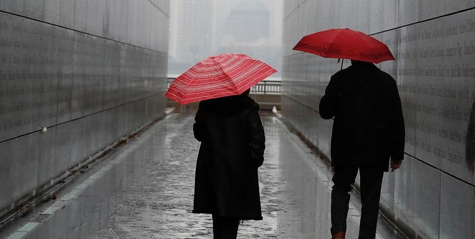FILE - In this Tuesday, Jan. 17, 2017, file photo, a couple walks through the Empty Sky Memorial during a rainy day at Liberty State Park,  in Jersey City, N.J. An age difference in your relationship doesn't just mean your favorite bands are from different decades. Even a small difference in years between two people can affect when you retire, how much you need to save and how those savings are invested. (AP Photo/Julio Cortez, File)