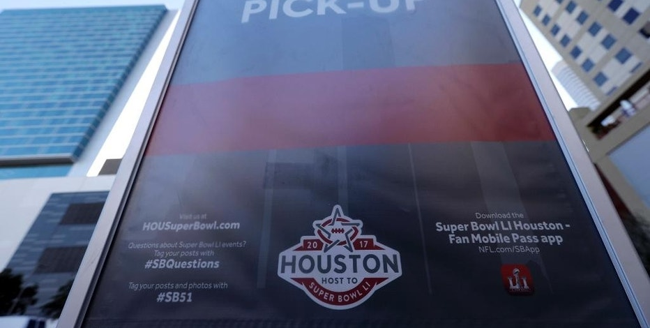 In this Tuesday, Jan. 30, 2017 photo, a sign marks an Uber designated pick-up point near the NFL Experience in downtown Houston. Thanks to the Super Bowl, people taking part in the festivities surrounding the game in Houston will have Uber as one of their transportation choices. The ride sharing service and the city had been at odds over rules regulating how the ride sharing services operates in Houston. (AP Photo/David J. Phillip)