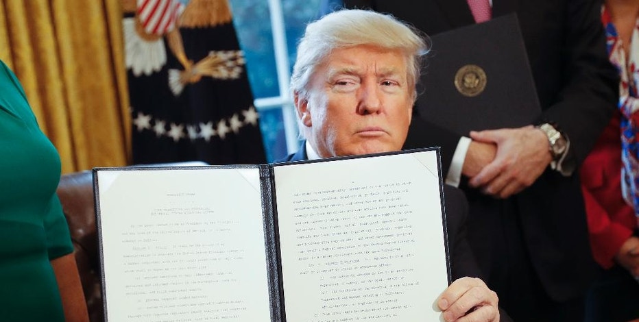 President Donald Trump holds up an executive order after his signing the order in the Oval Office of the White House in Washington, Friday, Feb. 3, 2017. The executive order that will direct the Treasury secretary to review the 2010 Dodd-Frank financial oversight law, which reshaped financial regulation after 2008-2009 crisis. (AP Photo/Pablo Martinez Monsivais)