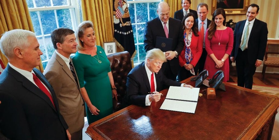 President Donald Trump prepares to sign an executive order in the Oval Office of the White House in Washington, Friday, Feb. 3, 2017. Trump signed an executive order that will direct the Treasury secretary to review the 2010 Dodd-Frank financial oversight law, which reshaped financial regulation after 2008-2009 crisis. At left is Vice President Mike Pence. (AP Photo/Pablo Martinez Monsivais)
