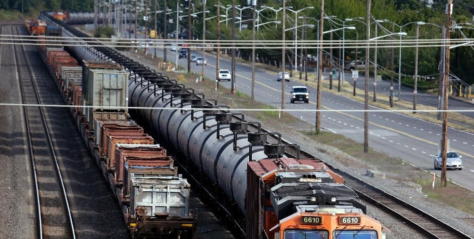 FILE - In this July 27, 2015, file photo, traffic passes one of two mile-long oil trains parked near the King County Airport in Seattle. More crude oil than ever is expected to move through Washington state, particularly since the Canadian government approved the Kinder Morgan pipeline project that will triple the number of tankers and barges plying local waters. Washington already has some of the toughest oil spill prevention and preparedness rules in the country but lawmakers say there are big gaps and that the rules need to be strengthened to keep up with the changing landscape. (AP Photo/Elaine Thompson, File)