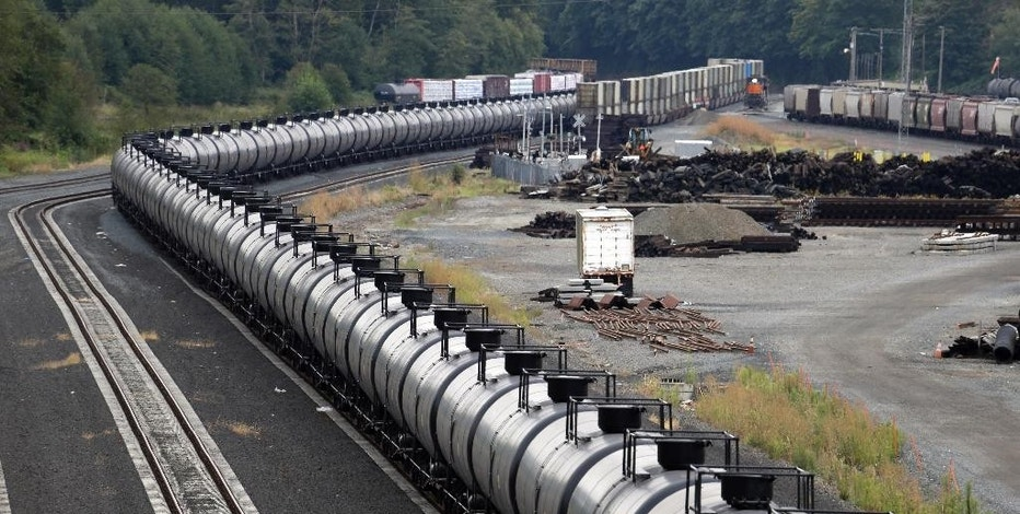 FILE - In this Sept. 2, 2014, file photo, a northbound oil train sits idled on tracks, stopped by protesters blocking the track ahead, in Everett, Wash. More crude oil than ever is expected to move through Washington state, particularly since the Canadian government approved the Kinder Morgan pipeline project that will triple the number of tankers and barges plying local waters. Washington already has some of the toughest oil spill prevention and preparedness rules in the country but lawmakers say there are big gaps and that the rules need to be strengthened to keep up with the changing landscape. (AP Photo/Elaine Thompson, File)