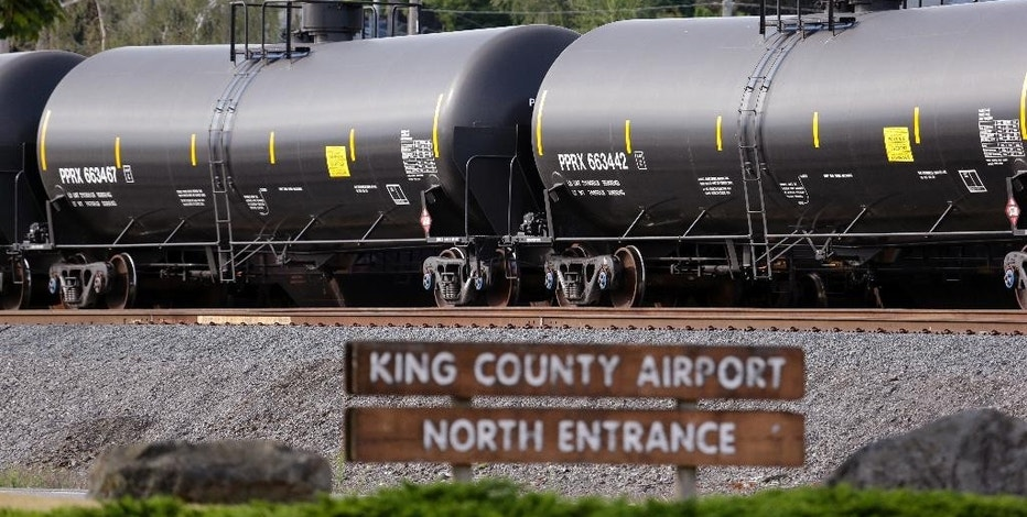 FILE - In this July 27, 2015, file photo, cars from one of two mile-long oil trains parked near the King County Airport are seen in Seattle. More crude oil than ever is expected to move through Washington state, particularly since the Canadian government approved the Kinder Morgan pipeline project that will triple the number of tankers and barges plying local waters. Washington already has some of the toughest oil spill prevention and preparedness rules in the country but lawmakers say there are big gaps and that the rules need to be strengthened to keep up with the changing landscape. (AP Photo/Elaine Thompson, File)