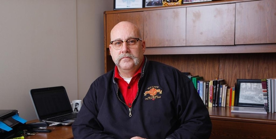 In a Jan. 26, 2017, photo, Monty Nye, a retired Meridian Township, Mich., firefighter still active in the Michigan Professional Fire Fighters Union and the International Association of Fire Fighters, poses in his office at the Michigan AFL-CIO in Lansing, Mich. Michigan is making a push to cut retiree health care and potentially move new public workers from pensions to 401(k) plans. (AP Photo/Al Goldis)
