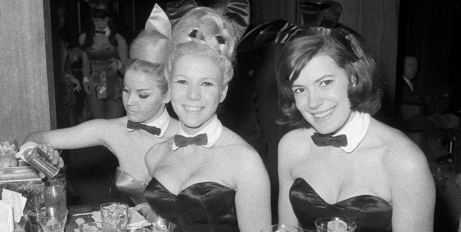 FILE - In this Jan. 15, 1963 file photo, Playboy Bunnies Elka Hellmann, from left, Monica Schaller and Sabrina Scharf serve drinks at New York's Playboy Club. The tightly corseted Playboy Bunnies, with rabbit tails and ears, will soon be back in business in New York City. Three decades after the original Playboy Club closed in Manhattan, a new club will debut later this year in a hotel a few blocks from Times Square. (AP Photo/John Lent, File)