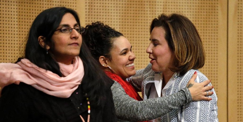 Seattle City Council member Debora Juarez, right, is embraced by Rachel Heaton, a Muckleshoot tribal member, as Council member Kshama Sawant stands nearby after Heaton gave both women gifts from the Native American community before a Council meeting Tuesday, Feb. 7, 2017, in Seattle. The City Council is scheduled to vote on whether to divest $3 billion in city funds from Wells Fargo over its funding of the Dakota Access Pipeline. (AP Photo/Elaine Thompson)