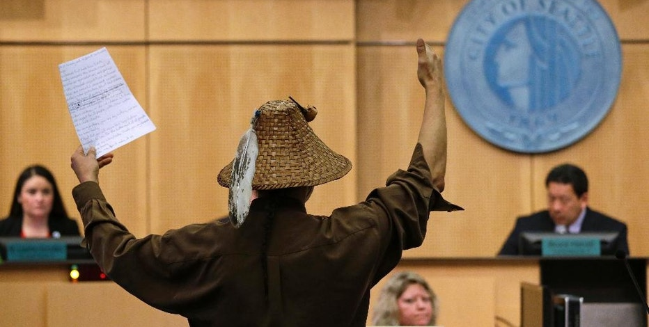 Paul Cheoketen, of the Wagner Saanich First Nations tribe, raises his arms as he ends his comments in favor of divestiture before a Seattle City Council meeting Tuesday, Feb. 7, 2017, in Seattle. The City Council is scheduled to vote on whether to divest $3 billion in city funds from Wells Fargo over its funding of the Dakota Access Pipeline. (AP Photo/Elaine Thompson)