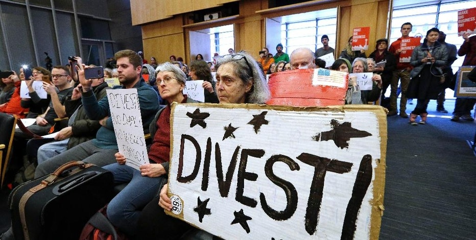 Cynthia Lynet holds a sign in favor of divestiture during a Seattle City Council meeting before a scheduled vote on whether to divest $3 billion in city funds from Wells Fargo over its funding of the Dakota Access Pipeline, Tuesday, Feb. 7, 2017, in Seattle. (AP Photo/Elaine Thompson)
