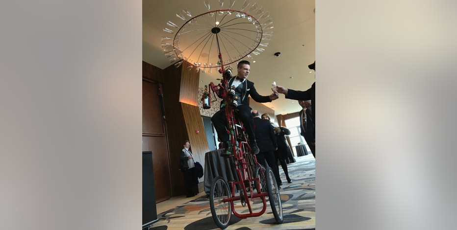 A server on a bicycle passes out champagne to guests attending the opening day at Rivers Casino and Resort Wednesday, Feb. 8, 2017 in Schenectady, N.Y. The Rivers Casino is the third of four new gambling facilities slated to begin operations in upstate New York. (AP Photo/David Klepper)