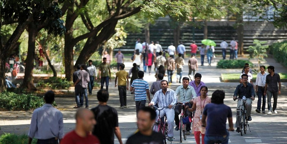 FILE - In this Jan. 11, 2013 file photo, employees of Infosys Technologies, the Indian technology outsourcing giant, move inside the company headquarters during a break after their quarterly financial results were announced in Bangalore, India. Speculation about tougher rules on so-called H-1B visas, used heavily by India's massive technology and outsourcing industries to send programmers and other computer specialists to the United States, sent tech stocks tumbling in India early February, 2017, and compounded concerns about the protectionist direction of U.S. policy after President Donald Trump temporarily suspended immigration from seven Muslim-majority countries. (AP Photo/Aijaz Rahi, File)