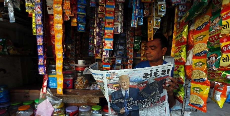 "FILE - In this Nov. 10, 2016, file photo, an Indian vendor who sells snacks and chewable tobacco reads a Gujarati language newspaper that has the headline ""this time Trump Government"" in Ahmadabad, India. The U.S. and India seem like a natural fit in the era of President Donald Trump: rambunctious democracies, led by populists, focused on economic growth and fighting radical Islam. It's a budding partnership that could be set back by a nuts-and-bolts dispute over employment visas. (AP Photo/Ajit Solanki, File)"
