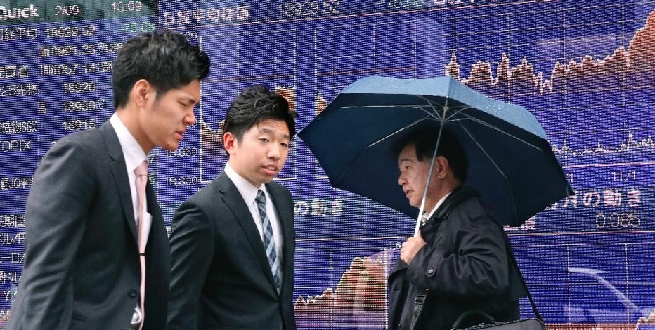 People walk past an electronic stock indicator of a securities firm in Tokyo, Thursday, Feb. 9, 2017. Asian shares mostly advanced Thursday after further gains on Wall Street that pushed the Nasdaq composite to a new record for the second day in a row. Japan's benchmark recovered lost ground after reports of strong machinery orders in December. (AP Photo/Shizuo Kambayashi)