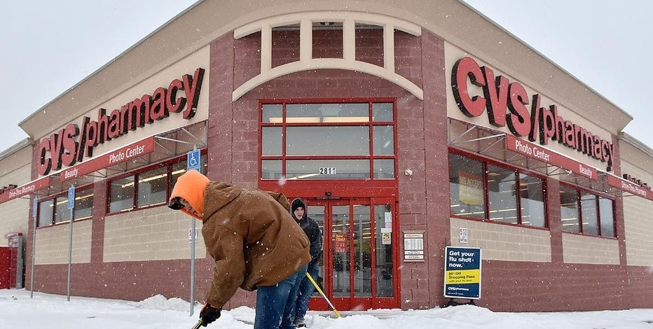 FILE - In this Friday, Jan. 22, 2016, file photo, workers for a private clearing company keep the walkways of a CVS Pharmacy clear of snow in Beckley, W.Va. On Thursday, Feb. 9, 2017, CVS Health Corp. reports financial earnings. (Brad Davis/The Register-Herald via AP, File)/The Register-Herald via AP)