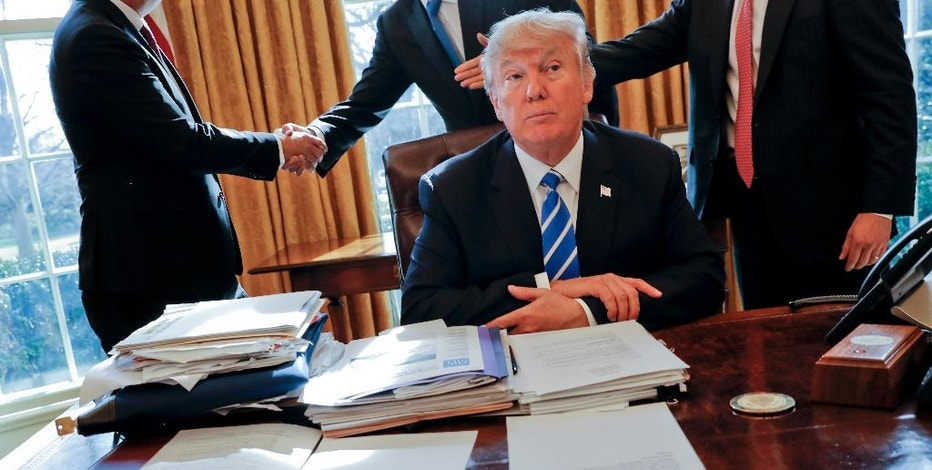 FILE - In this Wednesday, Feb. 8, 2017, file photo, President Donald Trump sits at his desk after a meeting with Intel CEO Brian Krzanich, left, and members of his staff in the Oval Office of the White House in Washington. Just three weeks into his administration, Trump and his allies are acting quickly to dismantle a web of regulations the government passed after the 2008 financial crisis to tighten oversight of banks and protect consumers and taxpayers. (AP Photo/Pablo Martinez Monsivais, File)